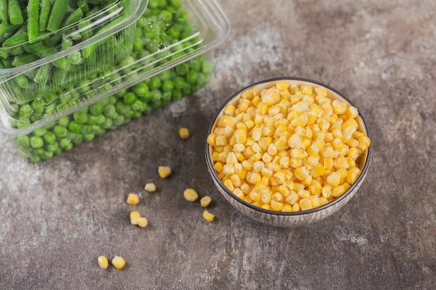 Plastikowy pojemnik z różnymi organicznymi mrożonymi warzywami na stole. zielony groszek, słodka kukurydza i pokrojona zielona fasolka w pudełku