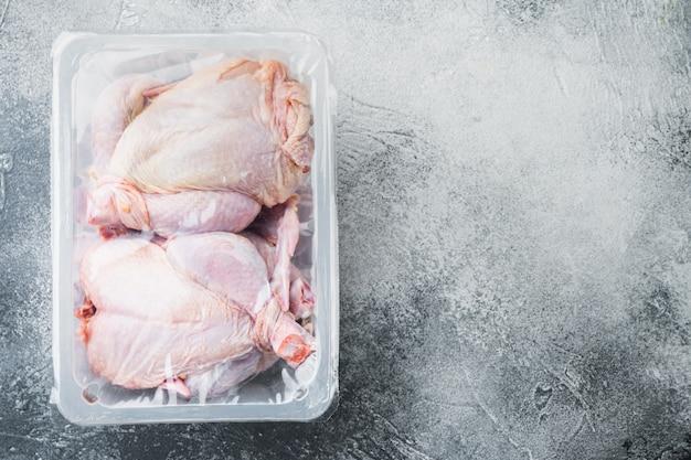 Plastikowy pojemnik z zestawem surowego kurczaka na szarym stole, widok z góry