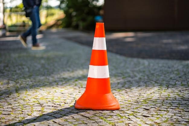Plastikowy pomarańczowy stożek parkingowy stojący na ulicy na niewyraźne tło męskich nóg.