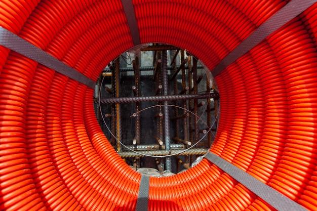 Plastikowy pomarańczowy wąż owinięty w zwój na placu budowy