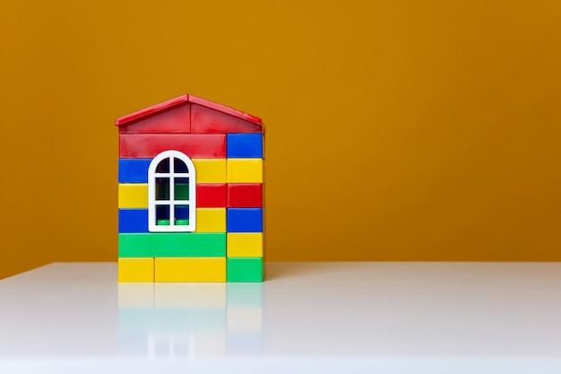 Plastikowy wielokolorowy domek wykonany z designerskich elementów na białym stole i jasnożółtej ścianie