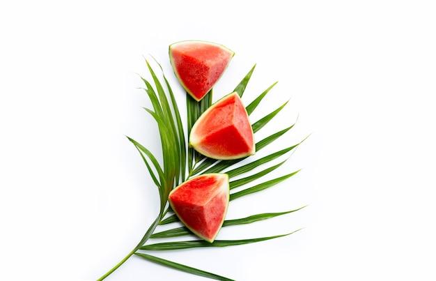 Plastry arbuza na tropikalnych liściach palmowych na białej powierzchni. widok z góry