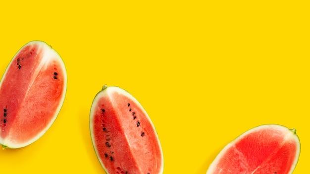 Plastry arbuza na żółtej powierzchni z miejscem na kopię