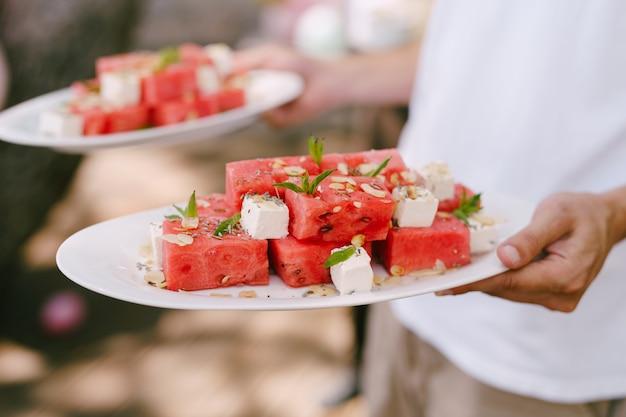 Plastry arbuza z serem i ziołami na talerzach