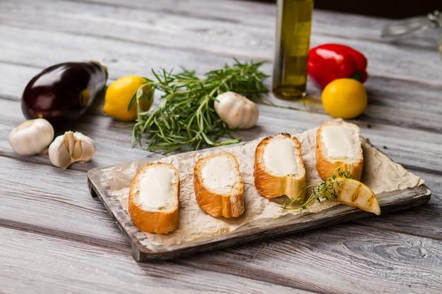Plastry bagietki z masłem. kawałek grillowanej cytryny. â¡ grzanki z masłem i tymiankiem. jak przygotować apetyczny posiłek.