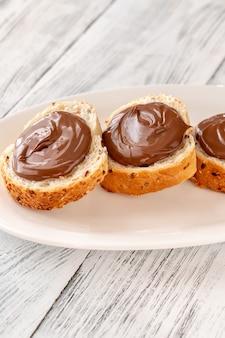 Plastry bagietki z pastą czekoladową na białym talerzu
