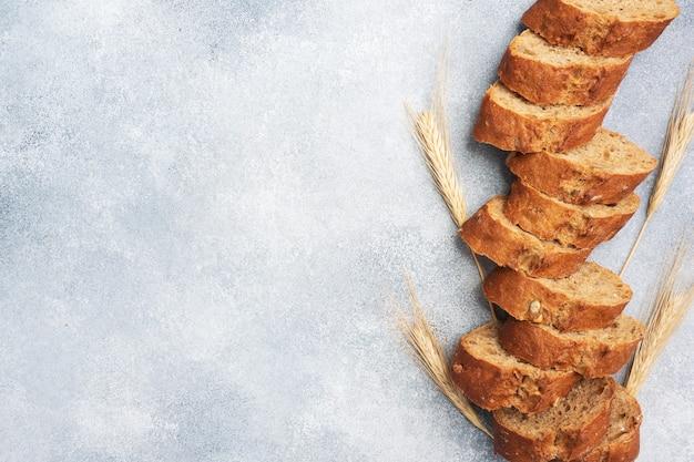 Plastry bagietki żytniej na szarym tle ze zbożami. chleb pełnoziarnisty, koncepcja zdrowej żywności. skopiuj miejsce.