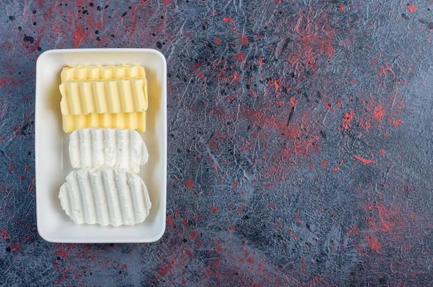 Plastry białego sera i masła w białym talerzu.