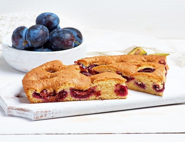 Plastry biszkoptowe ciasto śliwkowe na białej desce i świeże owoce