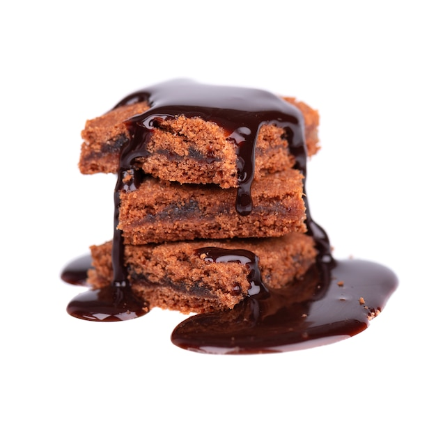 Plastry brownie, na białym tle, pokryte syropem z ciemnej czekolady.