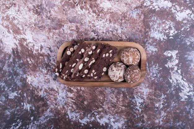 Plastry ciasta kakaowego i pierniki w drewnianym talerzu, widok z góry