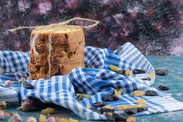 Plastry ciasta z suchymi winogronami na niebieskim ręczniku w kratkę.