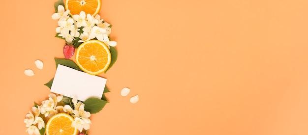 Plastry cytrusów i truskawek z ogrodowymi kwiatami jaśminu z liśćmi i pustą wizytówką na oran...