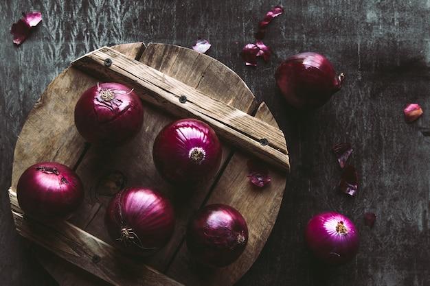 Plastry czerwonej cebuli na drewnianej desce z ciemnym tłem