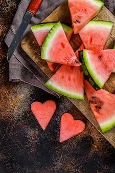 Plastry dojrzałego arbuza w kształcie serca. pojęcie miłości do arbuza. selektywne ustawianie ostrości