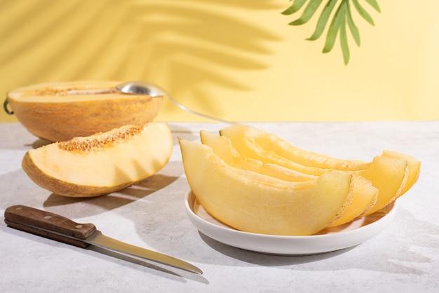 Plastry dojrzałego melona na białym talerzu na żółtym tle z pięknym cieniem z liścia.