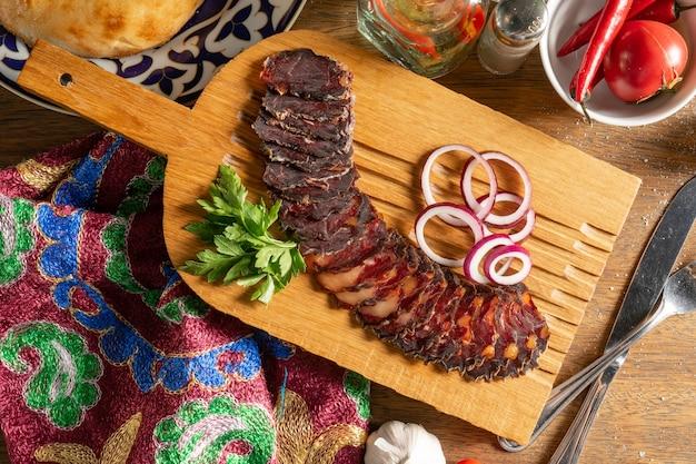 Plastry domowej kiełbasy z suszonego mięsa końskiego z kolendrą i czerwoną cebulą, pokrojone w plastry i podane na drewnianej desce do krojenia