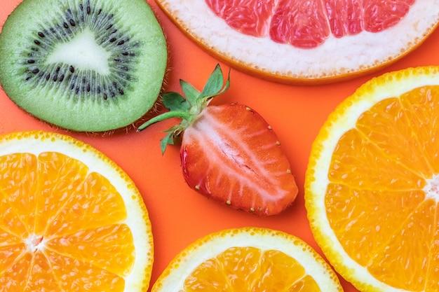Plastry grejpfruta, truskawki, kiwi i mandarynki. zabawa koncepcja lato.