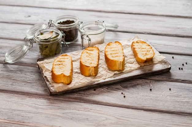 Plastry grillowanej bagietki. słoik z liśćmi laurowymi. najlepszy chleb na smaczne kanapki. zestaw niezbędnych przypraw.