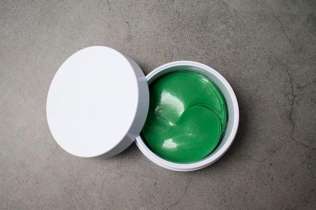 Plastry hydrożelowe nawilżają i odżywiają zieloną skórę wokół oczu. widok z góry na szarym tle.