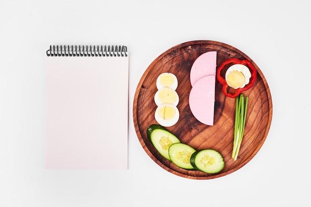 Plastry jajka na twardo, kiełbasy, zielonej cebuli, czerwonej papryki i ogórków na drewnianym talerzu z notatnikiem.