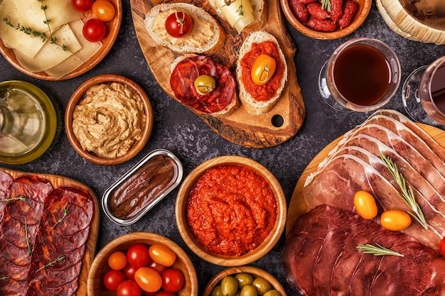 Plastry jamon, chorizo, kiełbasa, miski z oliwkami, pomidory, anchois, puree z ciecierzycy, ser.