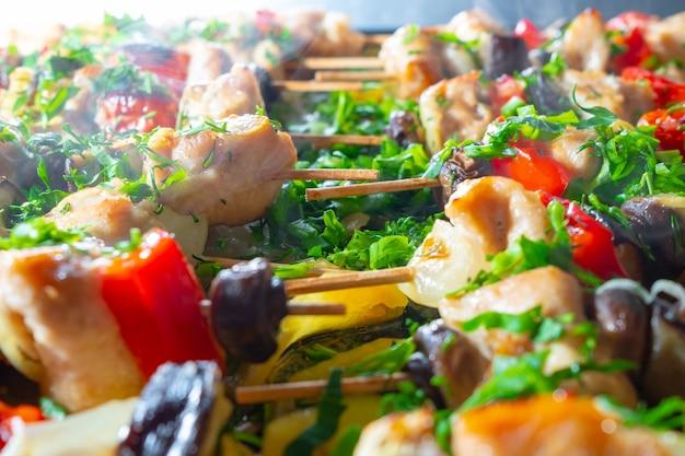 Plastry kurczaka, bakłażana, pomidora, słodkiej papryki i pieczarek nawleczone są na drewniane szaszłyki i smażone na różowo. pyszny przysmak ze świeżo posiekaną kolendrą, pietruszką i zieloną cebulką.