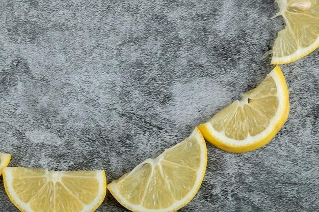 Plastry kwaśnej cytryny na szarym tle.