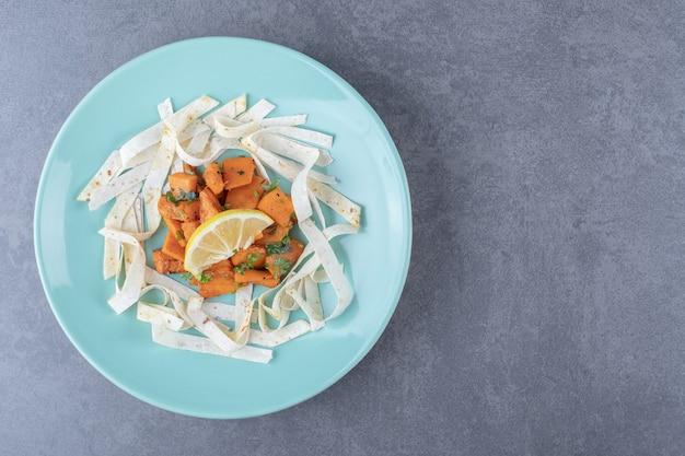 Plastry lawaszu i pieczona marchewka w talerzu, na marmurowej powierzchni.