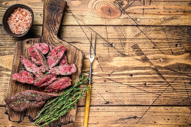 Plastry maczeta z grilla spódnica mięso wołowy stek na drewnianej desce do krojenia. drewniane tła. widok z góry. skopiuj miejsce.