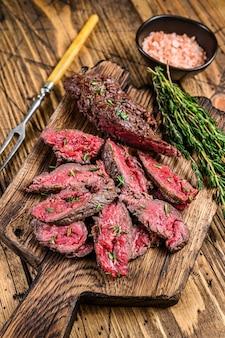 Plastry maczeta z grilla spódnica mięso wołowy stek na drewnianej desce do krojenia. drewniane tła. widok z góry.