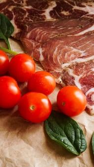 Plastry mięsa i pomidorki koktajlowe. składniki na kanapkę i bruschettę. gotowanie przekąsek. liście szpinaku. zdjęcie pionowe
