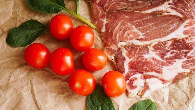 Plastry mięsa i pomidorki koktajlowe. składniki na kanapkę i bruschettę. gotowanie przekąsek. liście szpinaku.