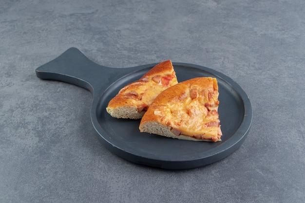 Plastry mieszanej pizzy na czarnej desce do krojenia.
