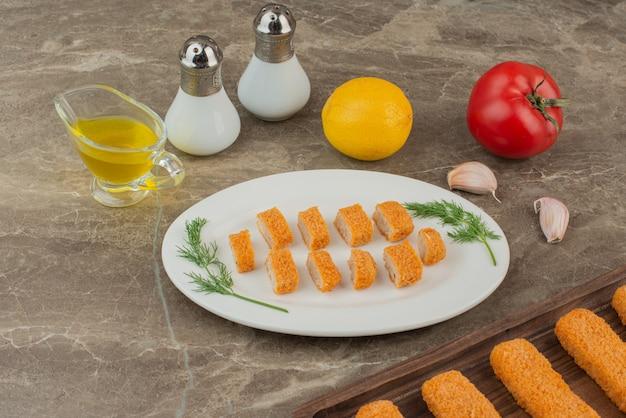 Plastry nuggetsów z kurczaka z pomidorem, cytryną, solą i pieprzem.
