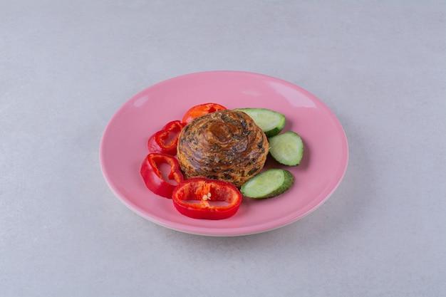 Plastry ogórka i pieprzu wokół ciastka na talerzu na ciemnej powierzchni