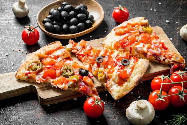 Plastry pachnącej pizzy z oliwkami, pomidorami i grzybami na ciemnym rustykalnym stole.