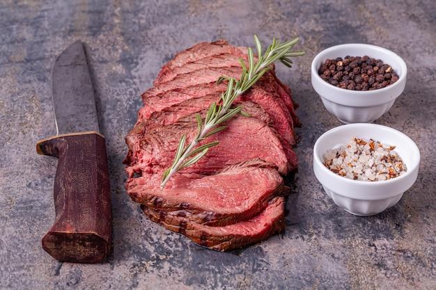 Plastry pieczonej wołowiny z rozmarynem, solą i pieprzem na szarym marmurze
