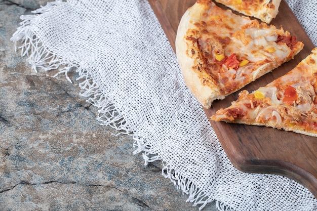 Plastry pizzy z roztopionym serem na wierzchu na drewnianej desce na kawałku białego juty