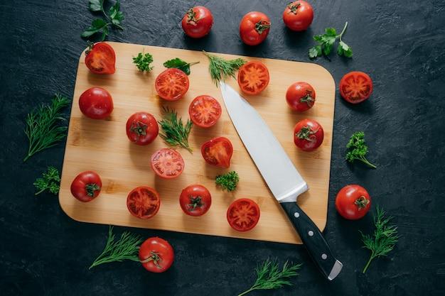 Plastry pomidorów cherry red z nożem na desce do robienia keczupu.