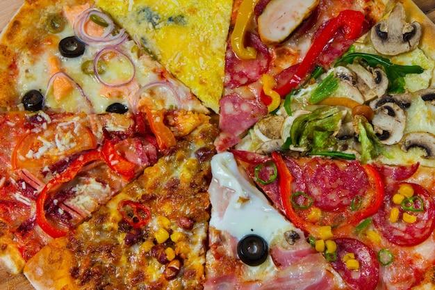 Plastry różnych rodzajów pizzy na białym tle