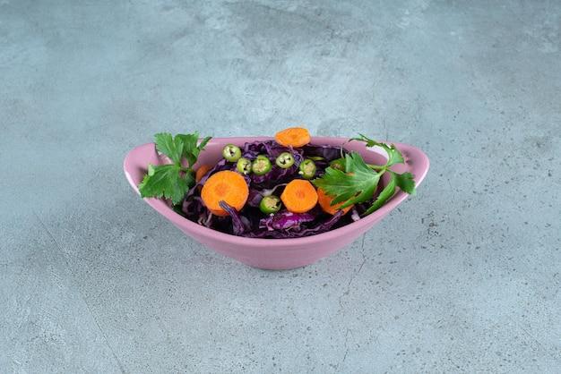 Plastry różnych warzyw i zieleni w misce różowy.