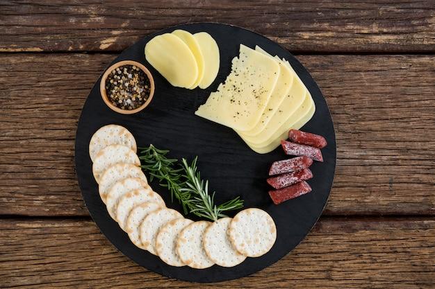 Plastry sera, rozmarynu i chipsów nacho na talerzu