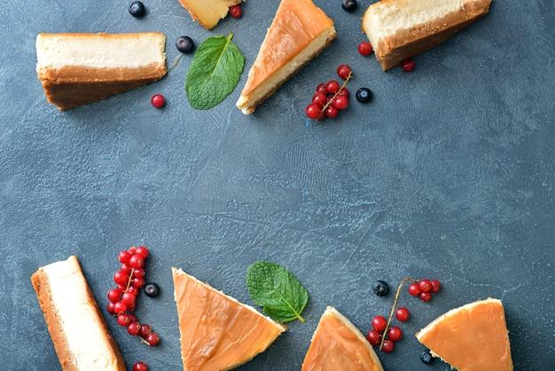 Plastry słodkiego sernika karmelowego z jagodami na ciemnym stole