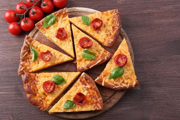 Plastry smacznej pizzy serowej z bazylią i pomidorkami koktajlowymi na stole z bliska