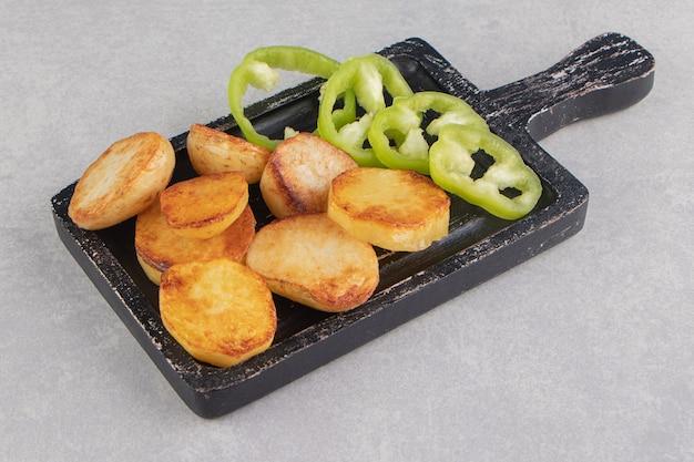 Plastry smażonych ziemniaków i papryki na czarnej tablicy.