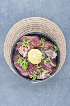 Plastry surowego mięsa i plasterki cytryny na czarnej płycie.