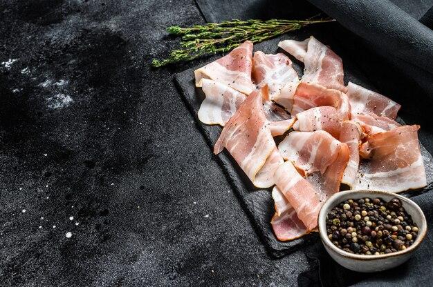 Plastry świeżego boczku wieprzowego z pieprzem i tymiankiem. organiczne surowe mięso. czarne tło. widok z góry. skopiuj miejsce