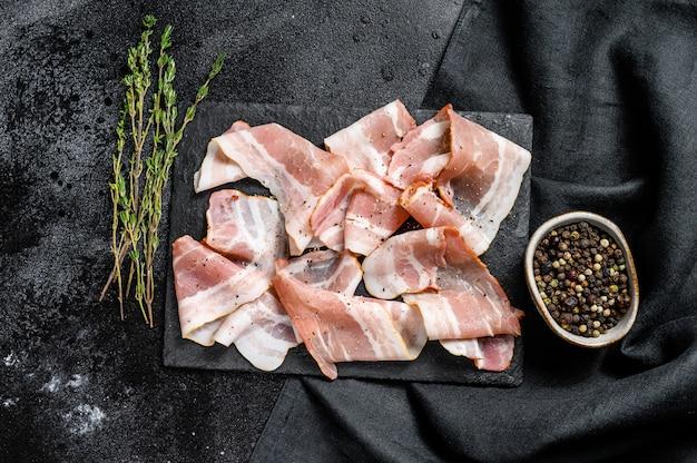 Plastry świeżego boczku wieprzowego z pieprzem i tymiankiem. organiczne surowe mięso. czarne tło. widok z góry