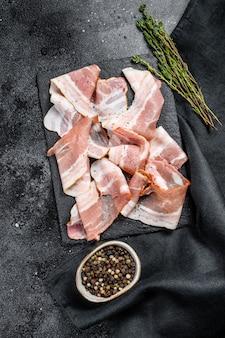 Plastry świeżego boczku wieprzowego z pieprzem i tymiankiem. organiczne surowe mięso. widok z góry